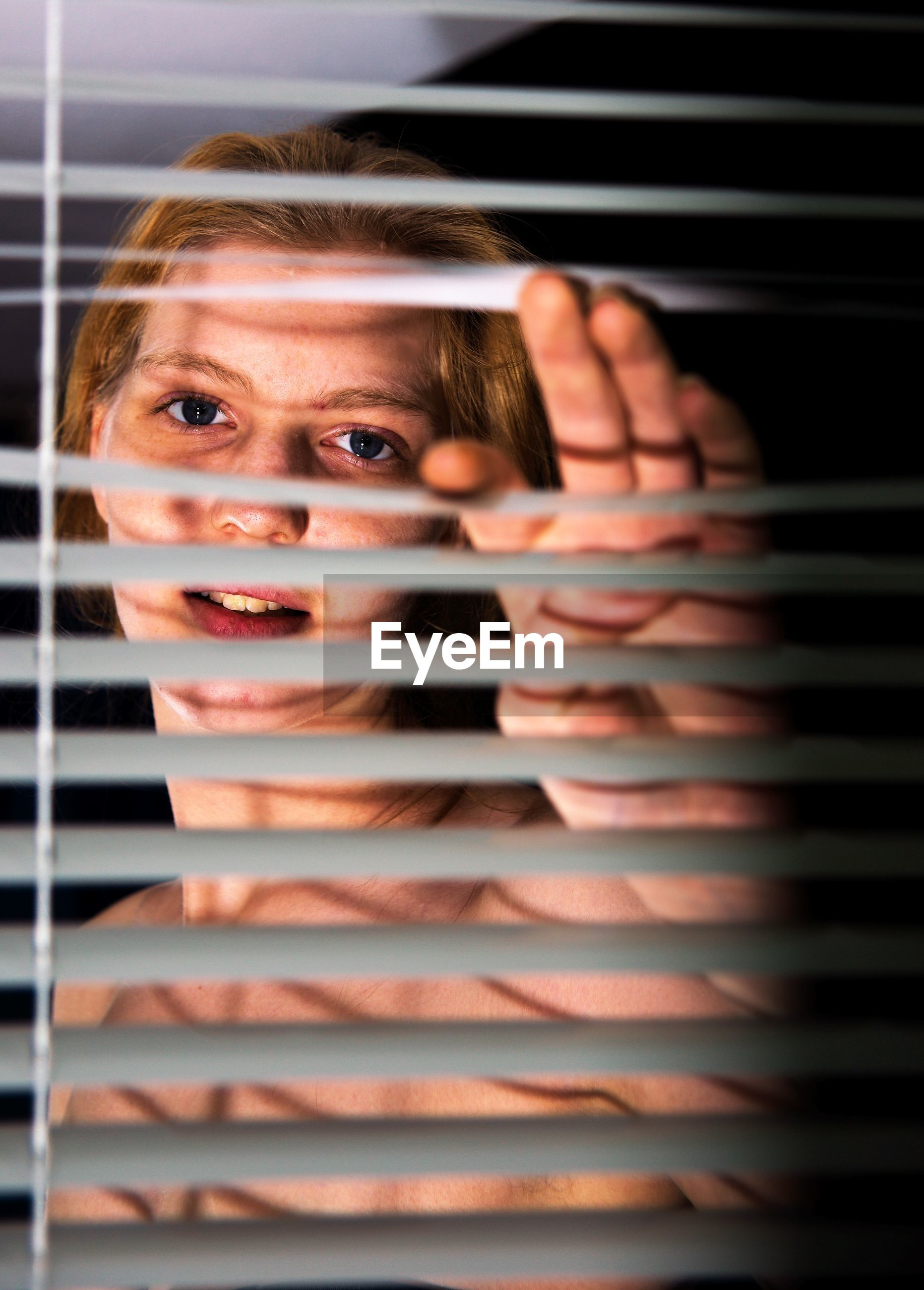 Portrait of young woman seen through blinds