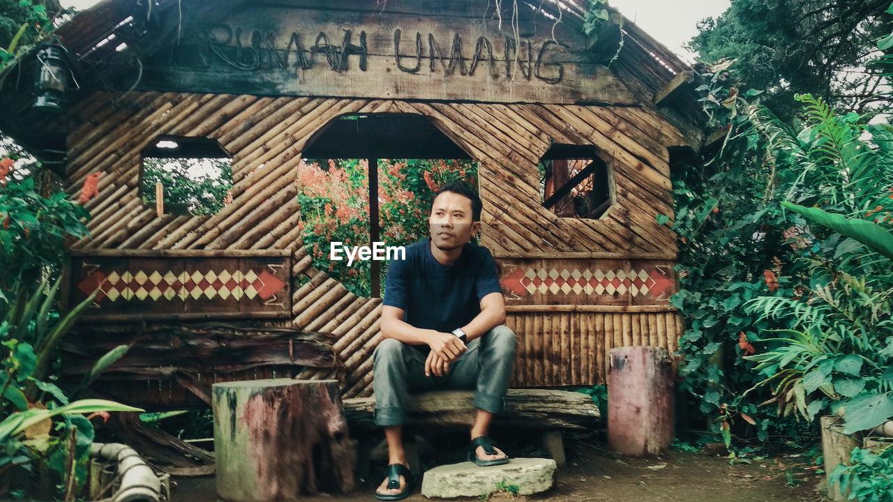 Young man sitting outside hut