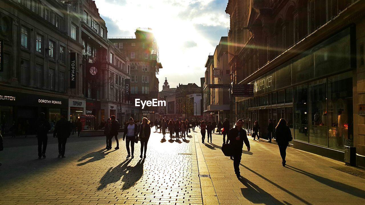 People Walking On City Street Against Sky