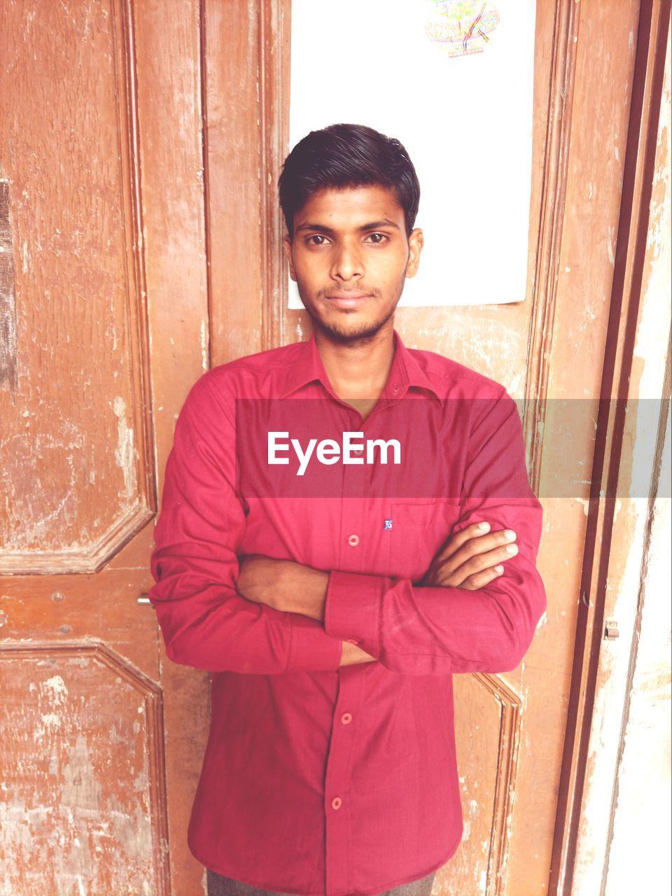 PORTRAIT OF YOUNG MAN STANDING AGAINST DOOR