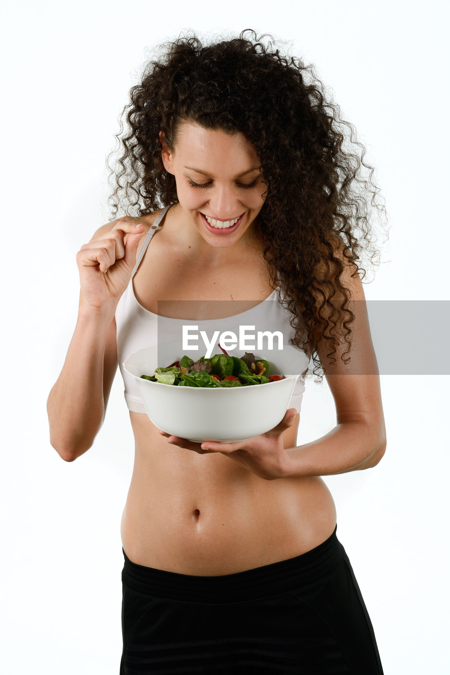 Smiling woman holding vegetables in bowl against white background