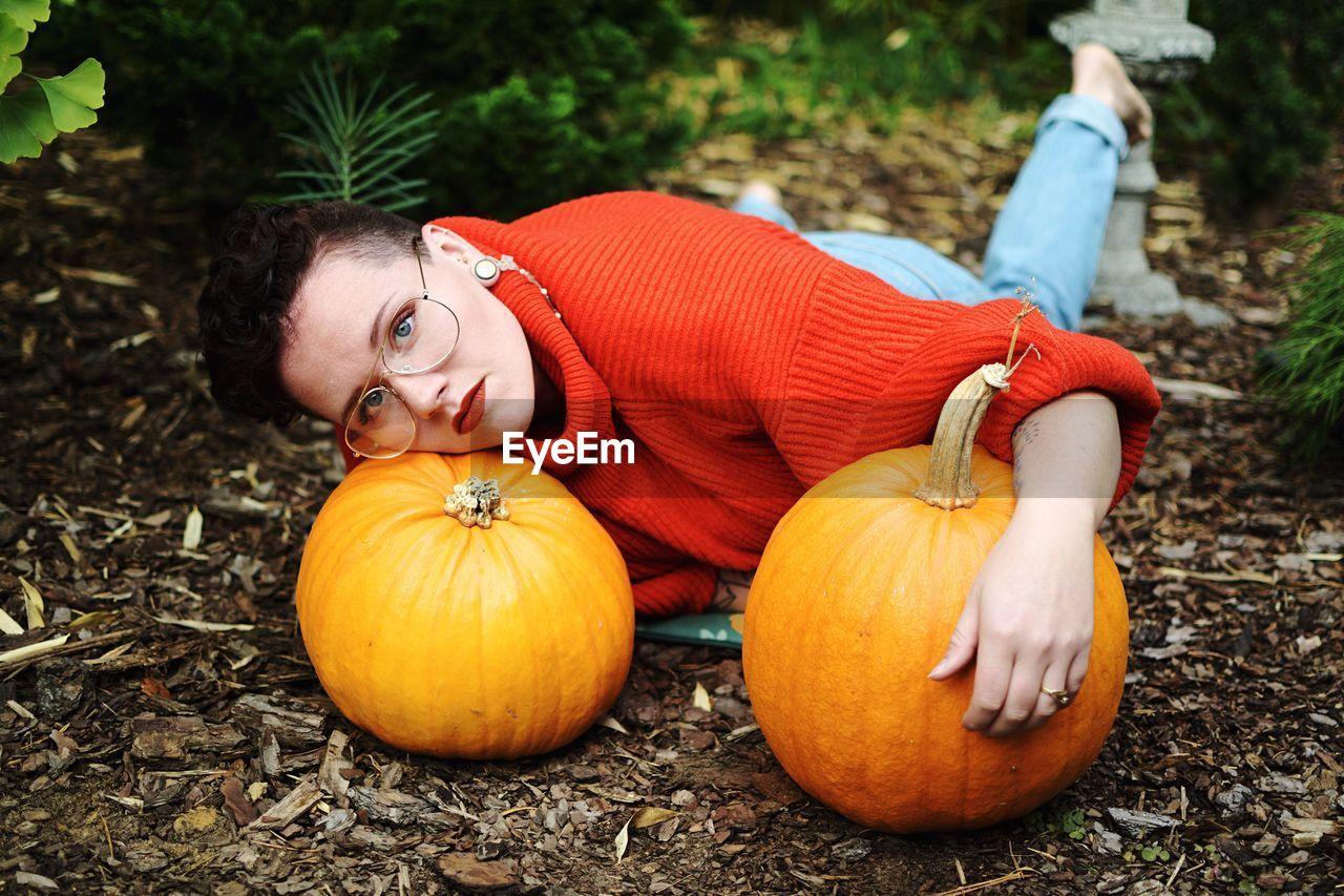 Portrait of woman lying with pumpkins on field