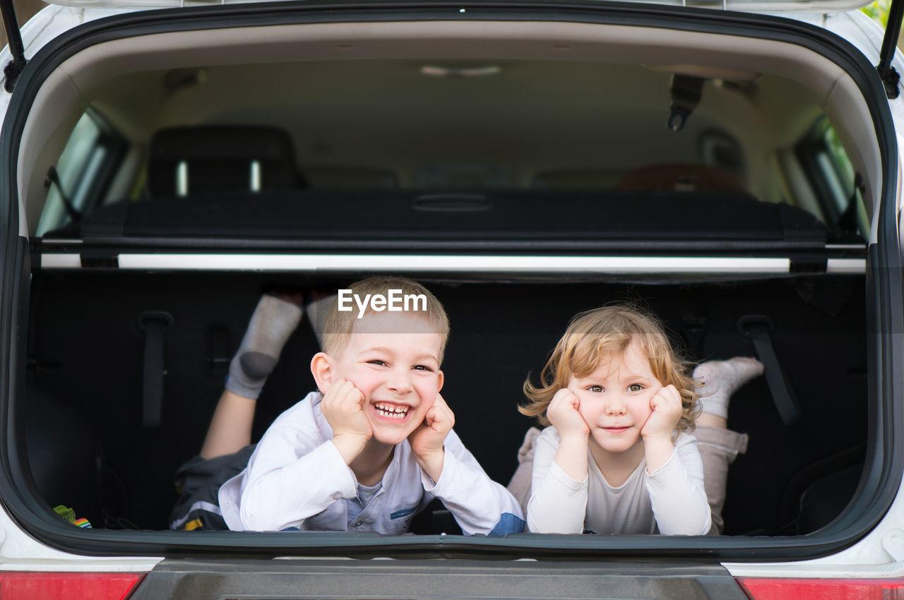 Portrait of cute sibling in car trunk