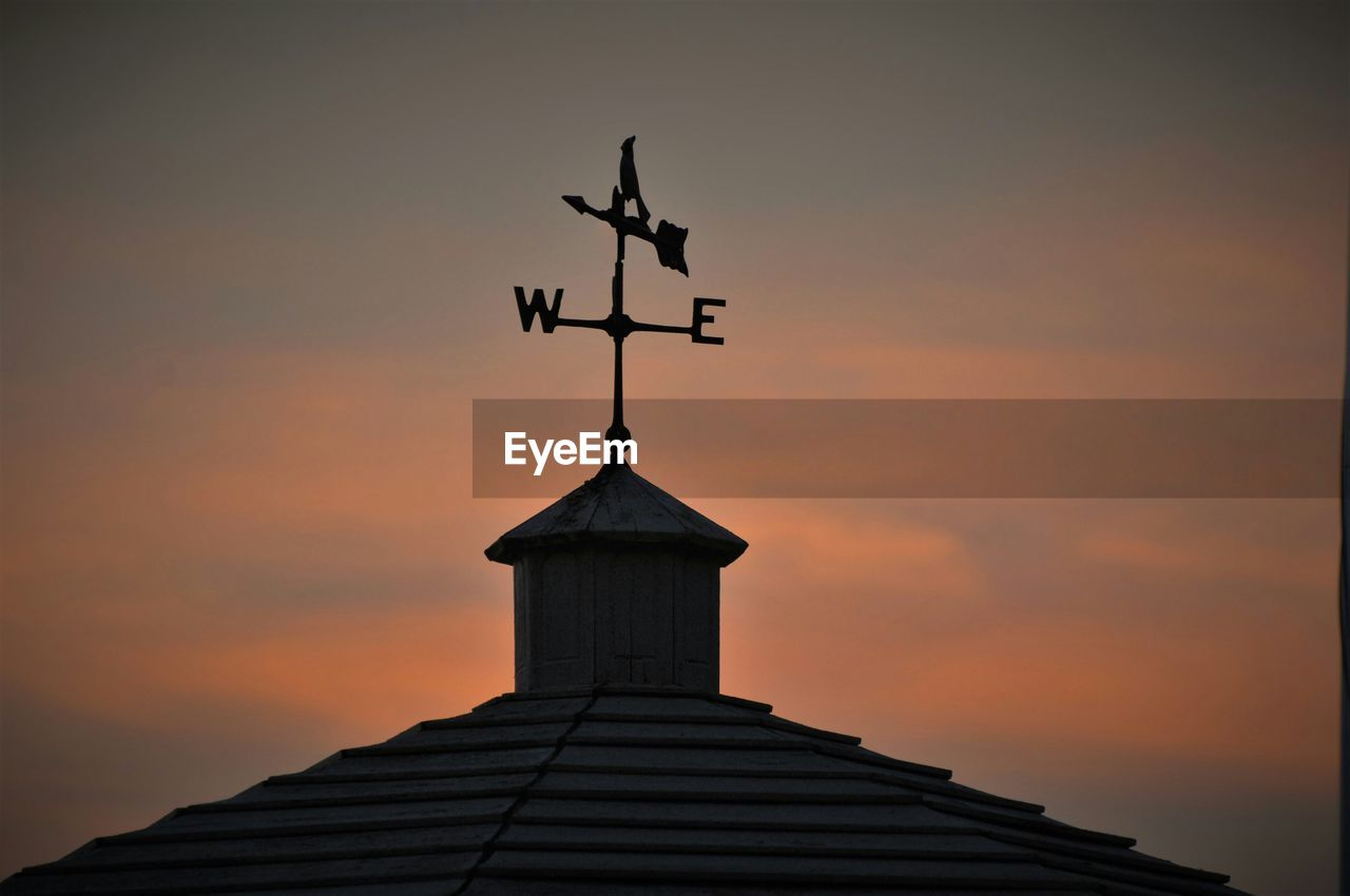 Low Angle View Of Weather Vane On Building Against Cloudy Sky During Sunset