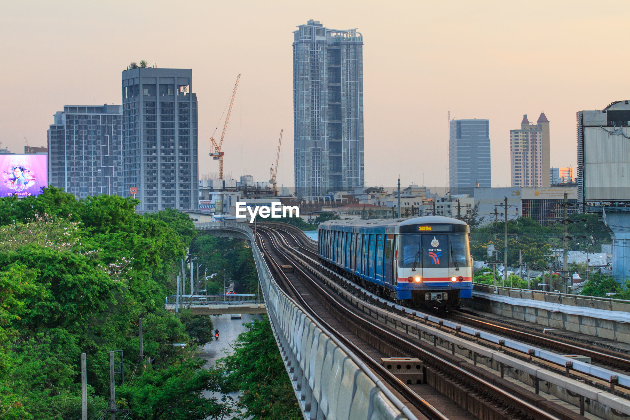 Train on railroad tracks against buildings in city during sunset
