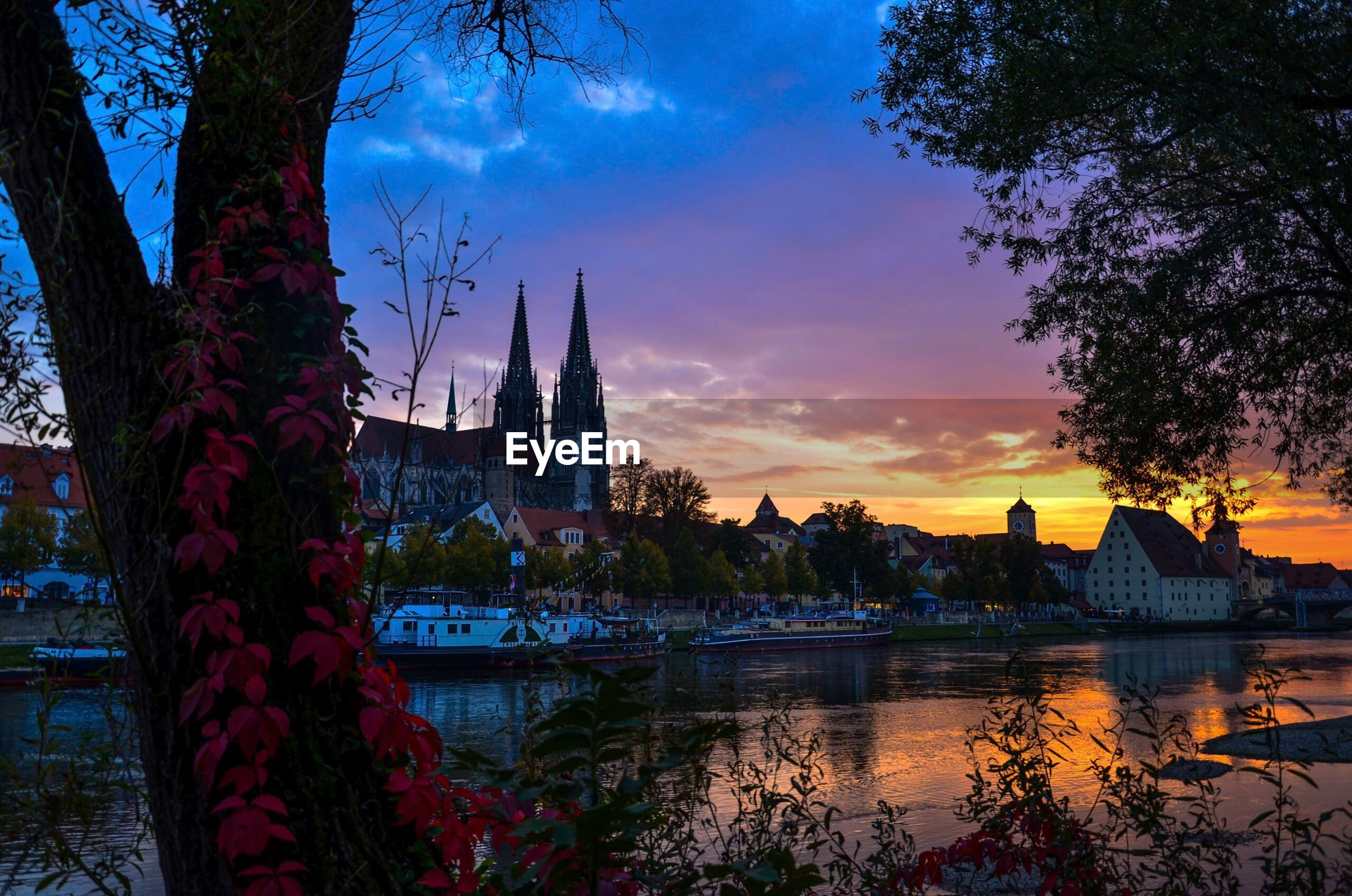 architecture, building exterior, built structure, sky, sunset, tree, water, city, river, bare tree, cloud - sky, place of worship, reflection, tower, orange color, famous place, lake, travel destinations, religion, spirituality