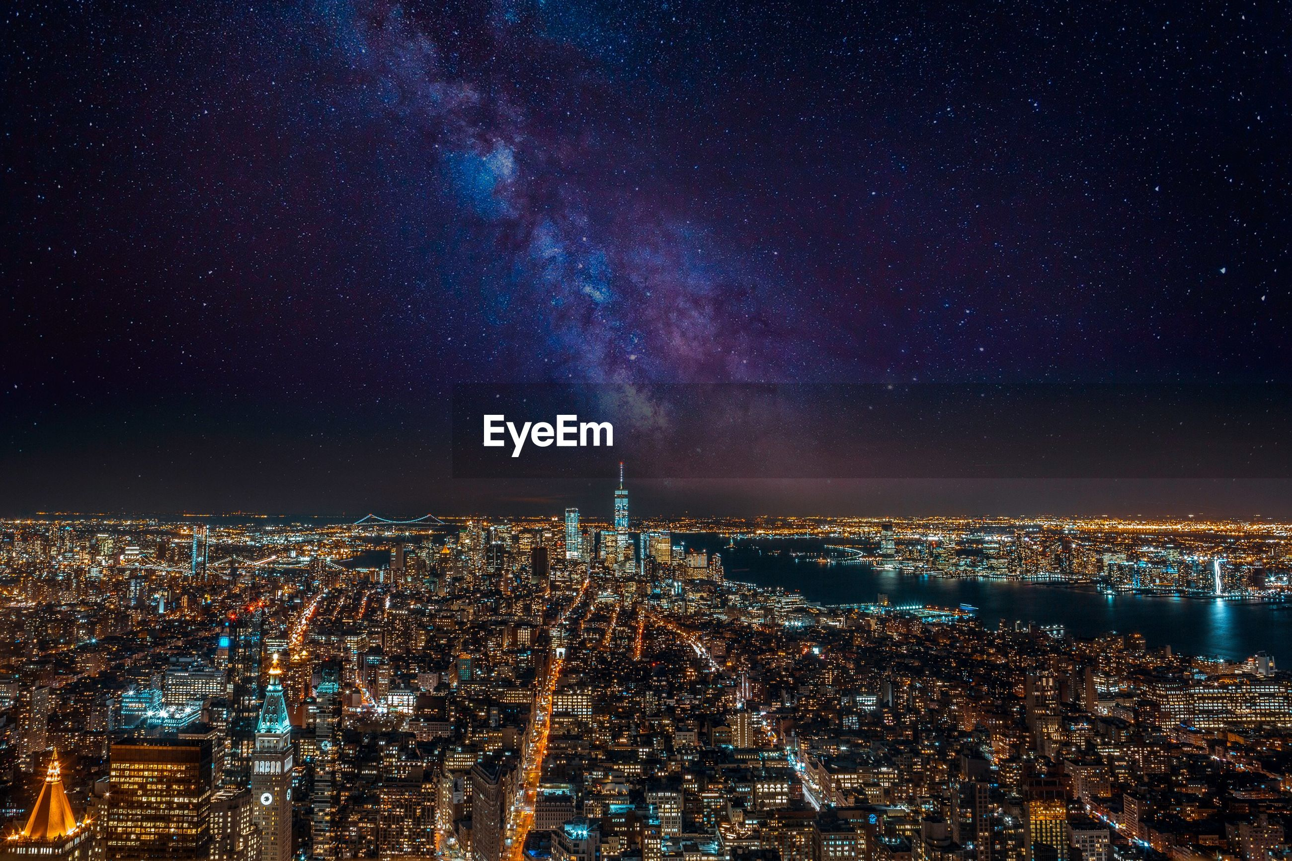 AERIAL VIEW OF ILLUMINATED CITY AGAINST SKY