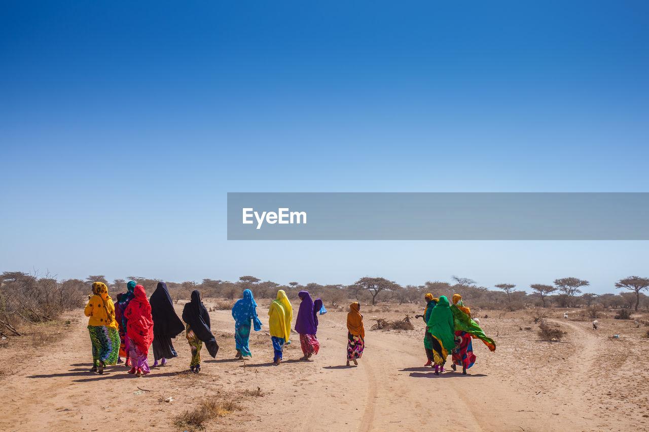 Rear View Of Women Wearing Scarfs While Walking In Desert Against Sky