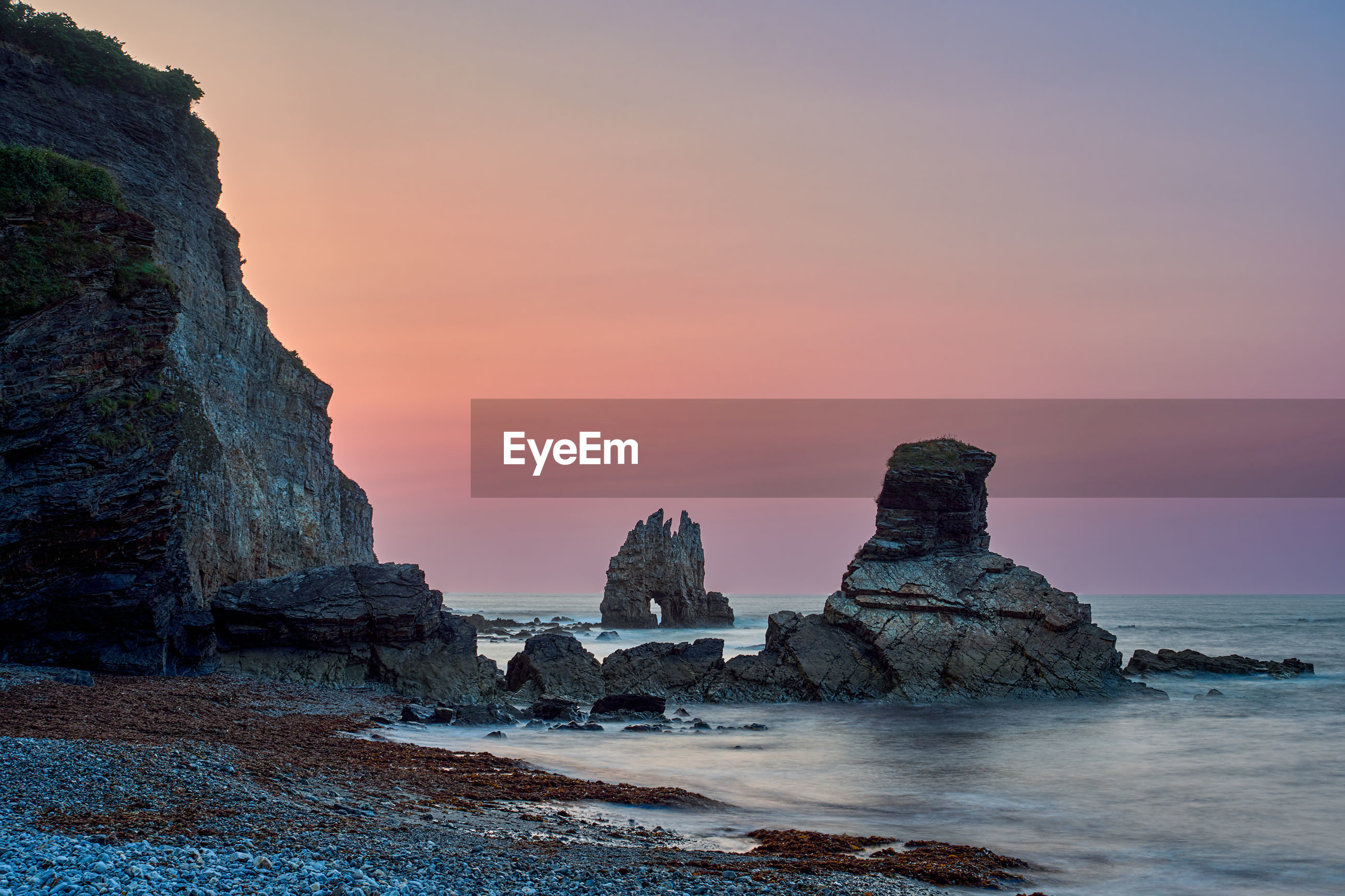 ROCK FORMATION ON BEACH AGAINST SKY AT SUNSET