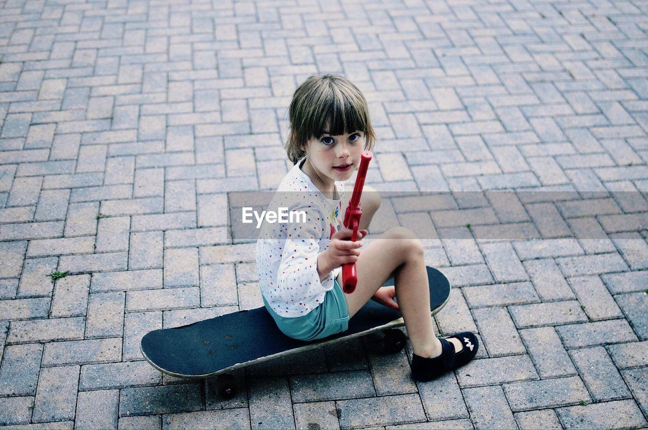 Portrait of girl holding toy gun while sitting on skateboard