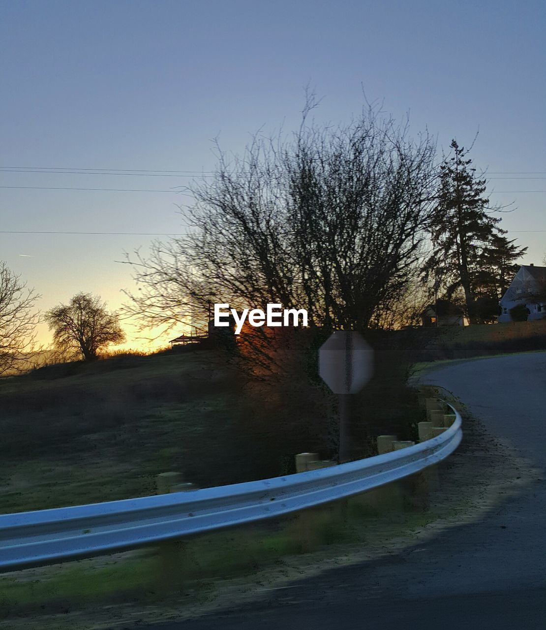 sky, tree, plant, road, nature, transportation, no people, bare tree, clear sky, sunset, tranquility, mode of transportation, dusk, beauty in nature, outdoors, scenics - nature, the way forward, tranquil scene, barrier, architecture