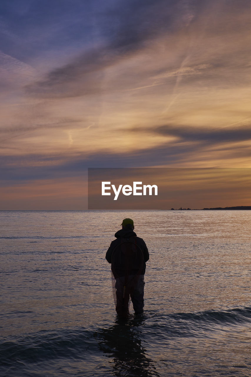 water, sea, sky, rear view, sunset, cloud - sky, beauty in nature, standing, scenics - nature, one person, real people, leisure activity, horizon over water, horizon, waterfront, men, nature, lifestyles, beach, outdoors, looking at view