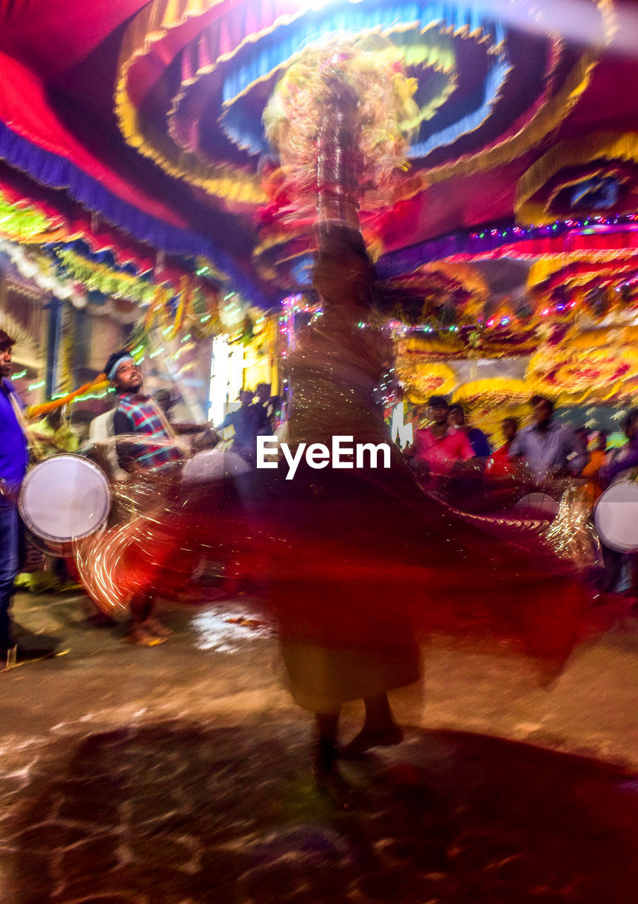 arts culture and entertainment, amusement park, leisure activity, blurred motion, enjoyment, real people, fun, motion, amusement park ride, carousel, lifestyles, night, carnival, rear view, men, illuminated, multi colored, celebration, full length, outdoors, women, people