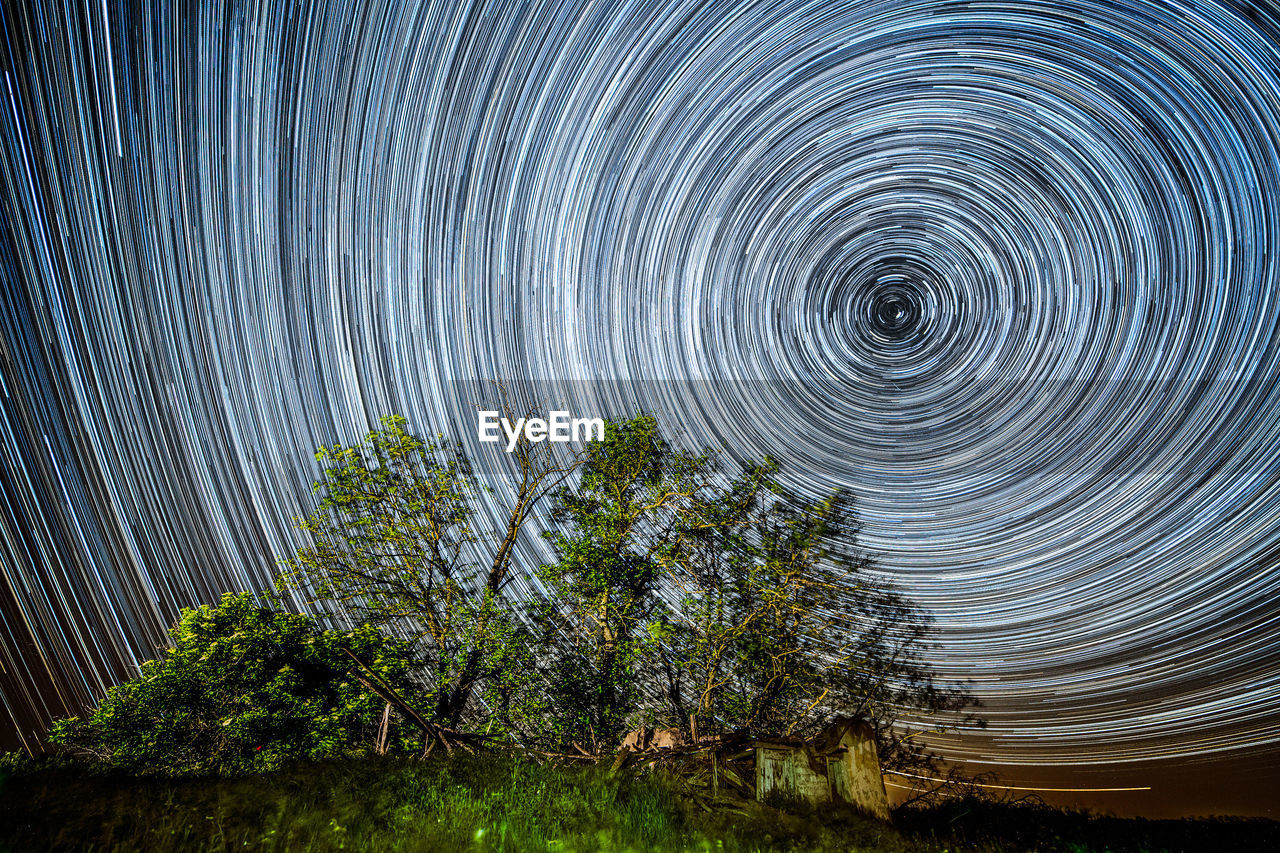 Trees on field against star trails at night