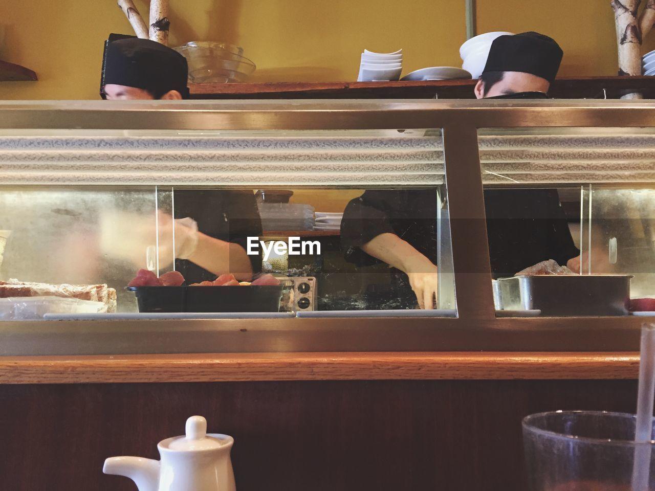 Chefs Working In Kitchen At Restaurant