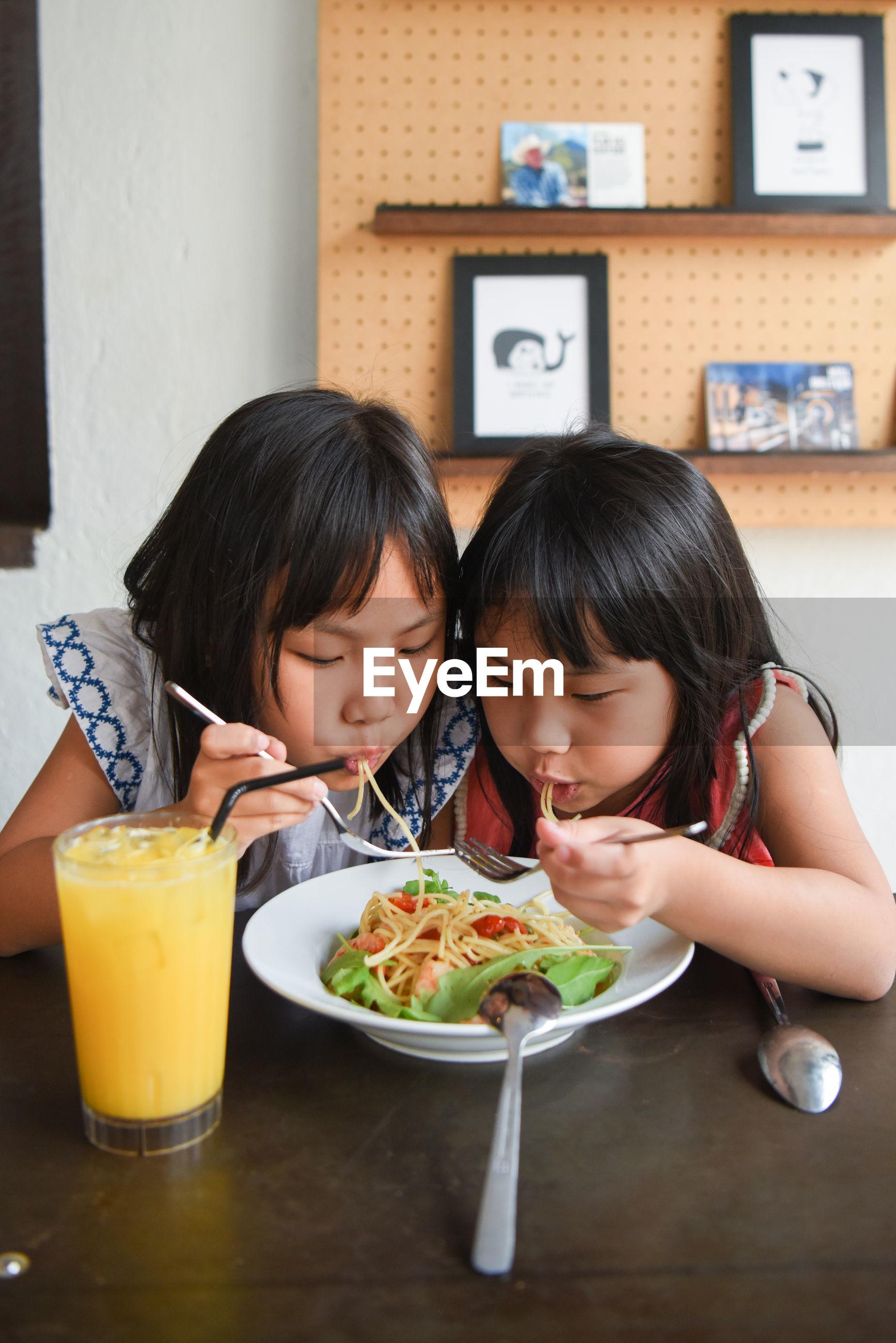Two girls eating pasta
