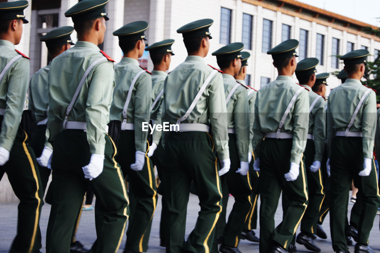 group of people, government, clothing, uniform, military, army soldier, armed forces, real people, men, day, standing, military uniform, crowd, large group of people, in a row, rear view, outdoors, celebration, full length, marching, marching band