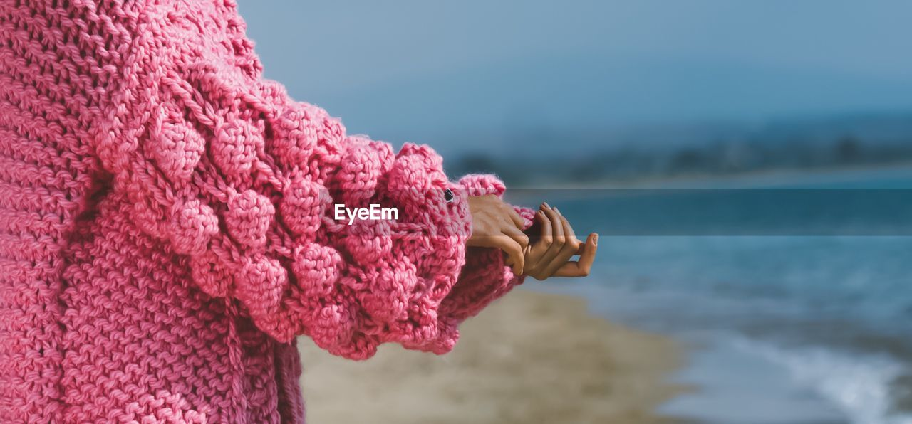 Close-Up Of Hand On Pink Sweater On A Beach