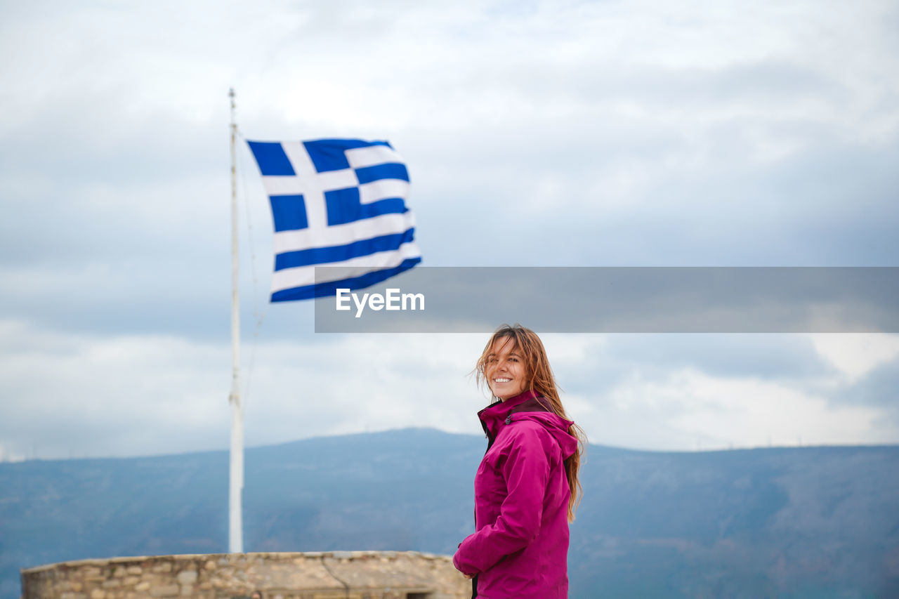 Smiling Woman Standing By Flag Against Sky