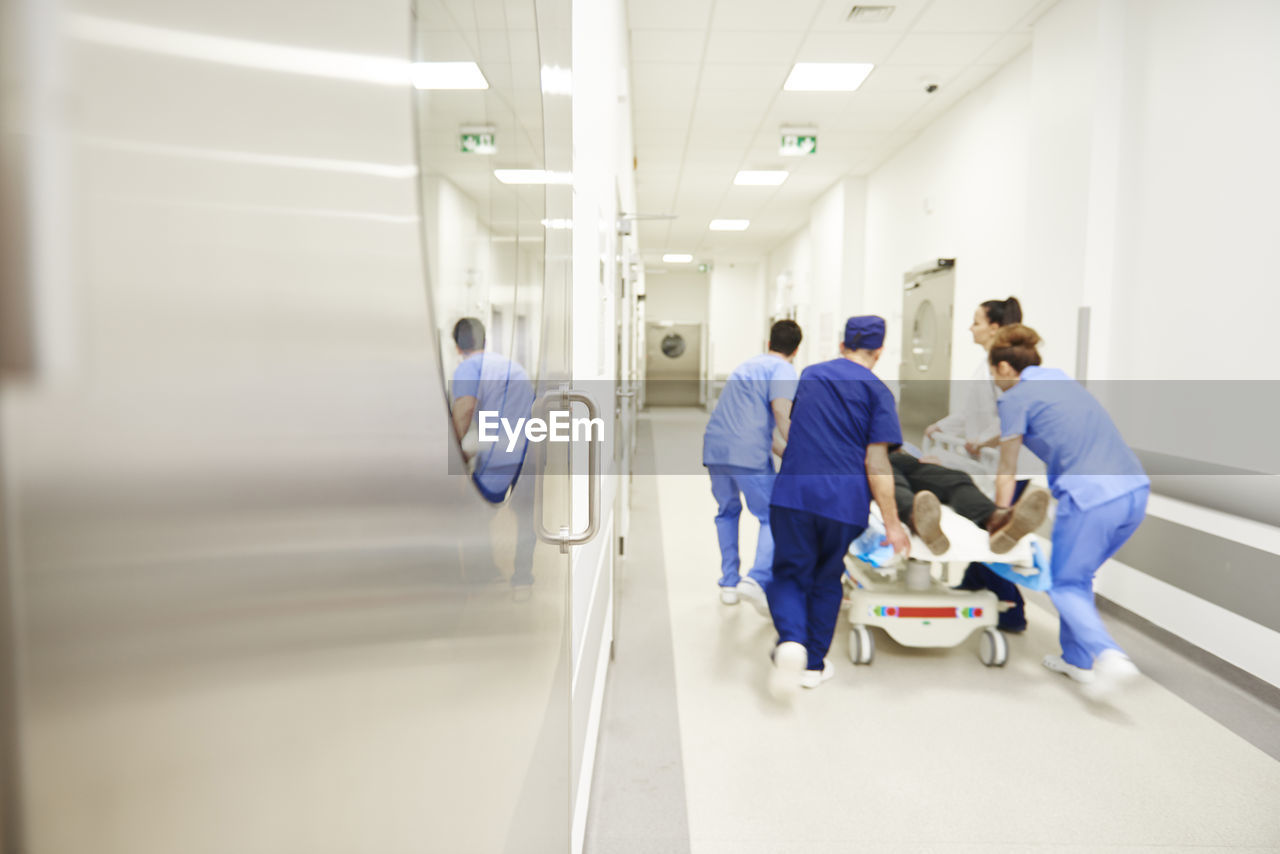healthcare and medicine, hospital, doctor, occupation, group of people, scrubs, full length, adult, teamwork, corridor, nurse, arcade, indoors, men, cooperation, care, architecture, responsibility, expertise, healthcare worker, coworker