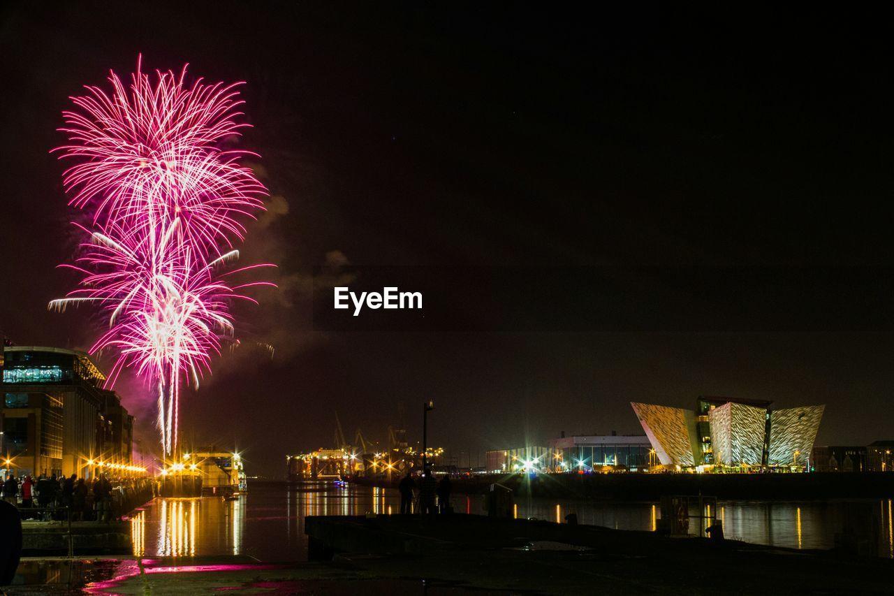 Firework display by titanic belfast against sky at dusk