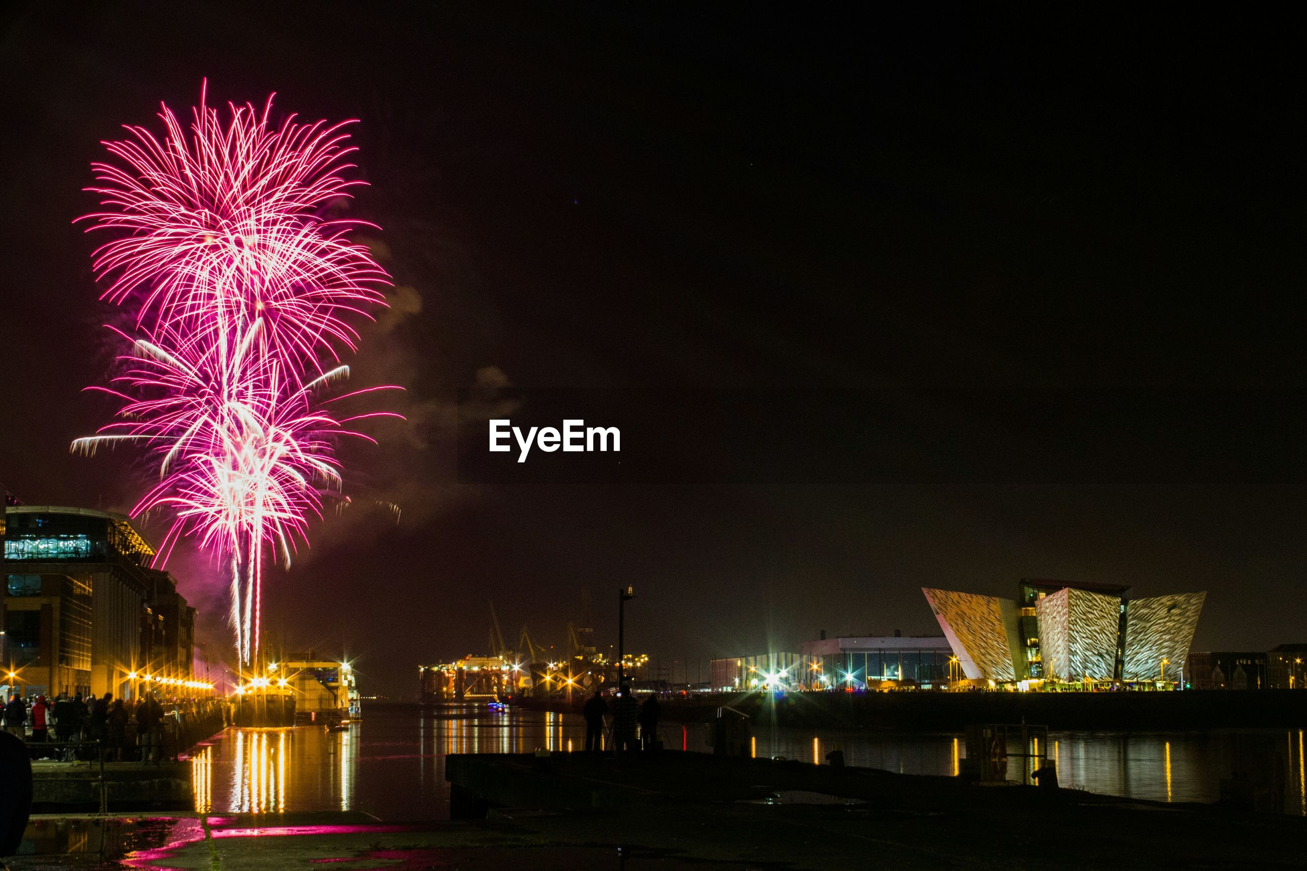 Firework display by titanic belfast against sky at dusk