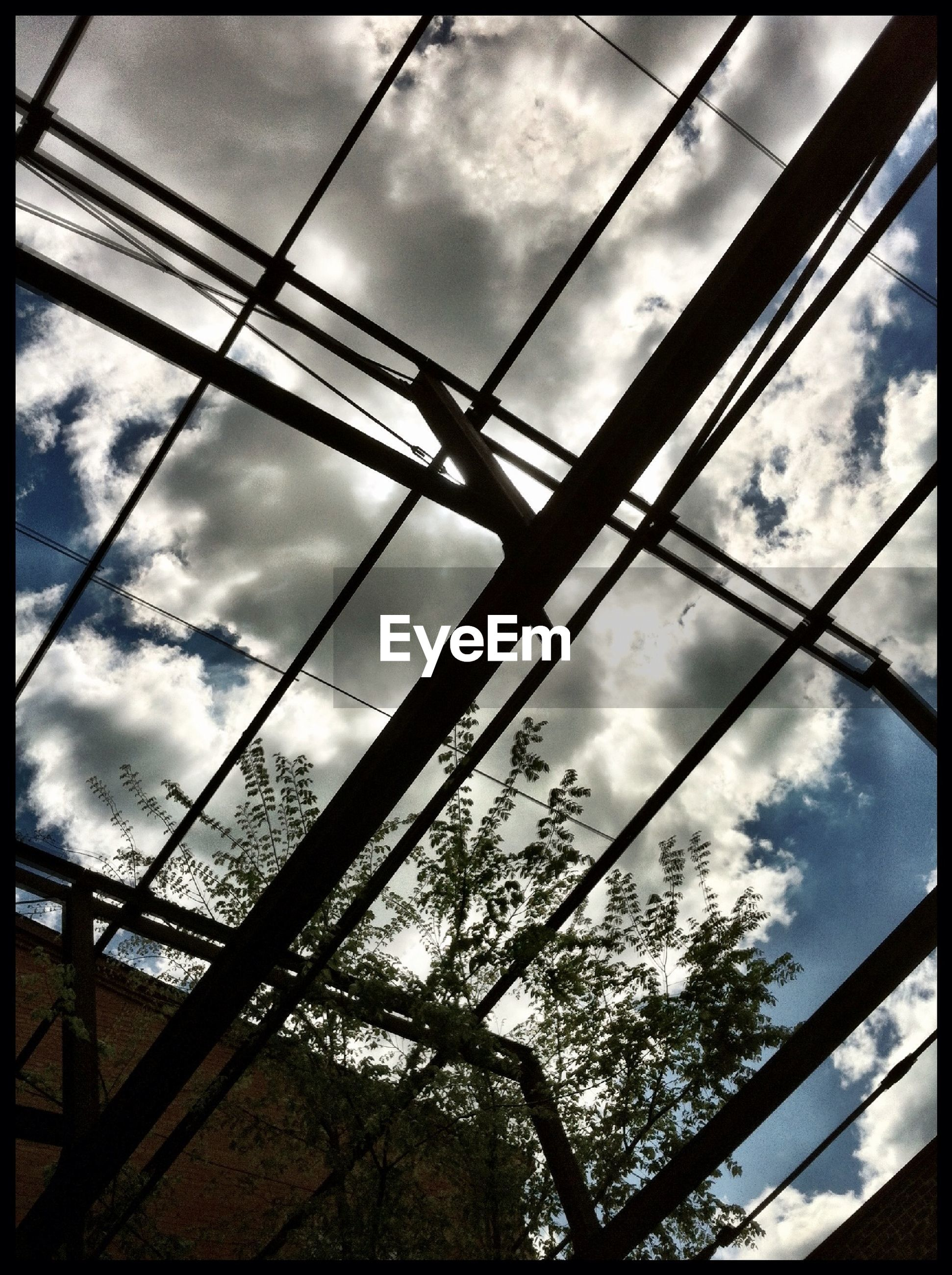 sky, low angle view, cloud - sky, built structure, cloudy, architecture, cloud, connection, transfer print, building exterior, tree, bridge - man made structure, auto post production filter, day, power line, overcast, weather, no people, outdoors, cable