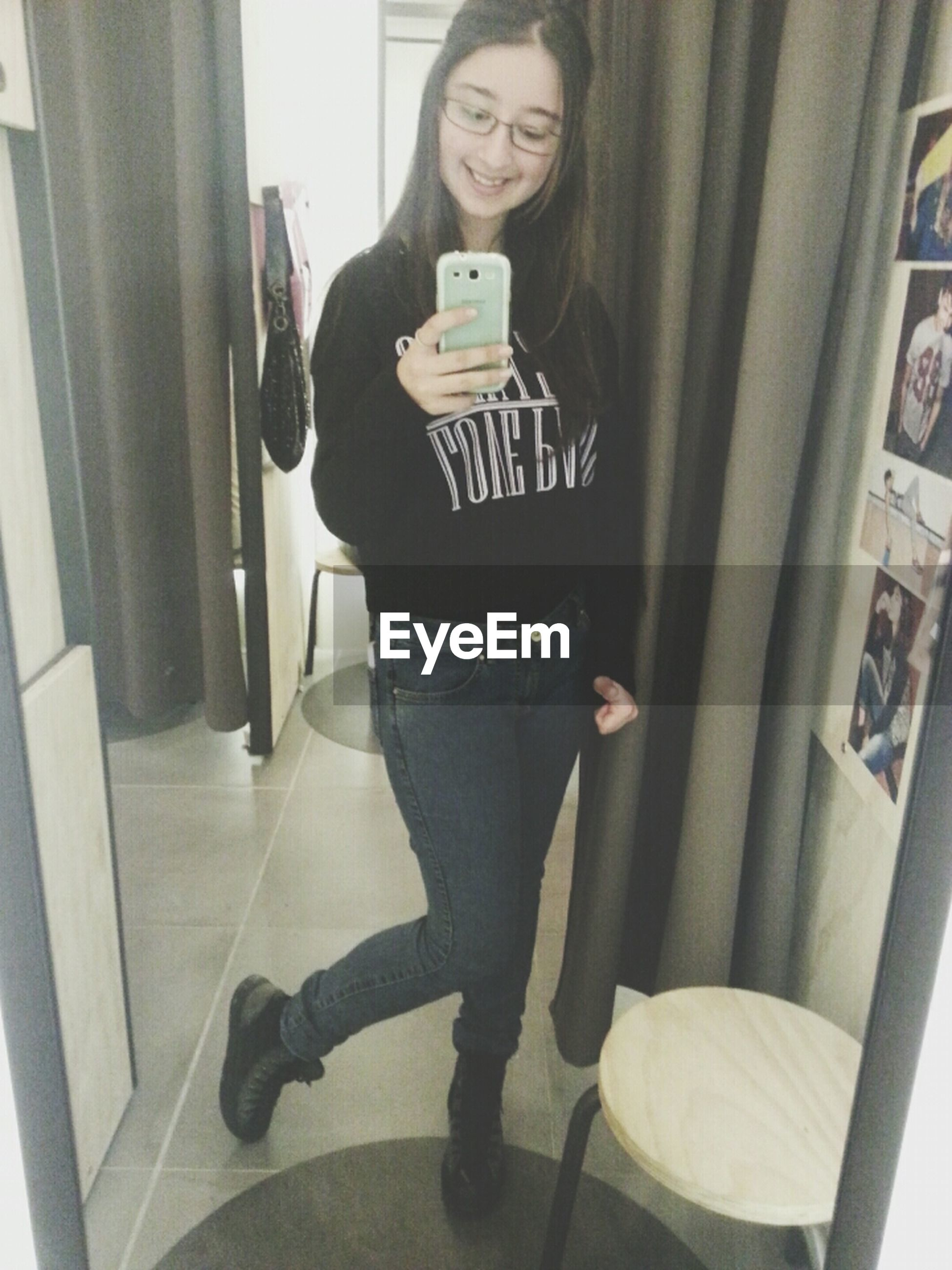 indoors, young adult, lifestyles, person, casual clothing, sitting, home interior, leisure activity, young women, front view, wireless technology, three quarter length, mirror, standing, technology, reflection, table, chair