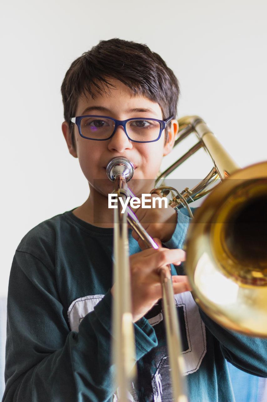 Portrait of cute boy playing trumpet against wall