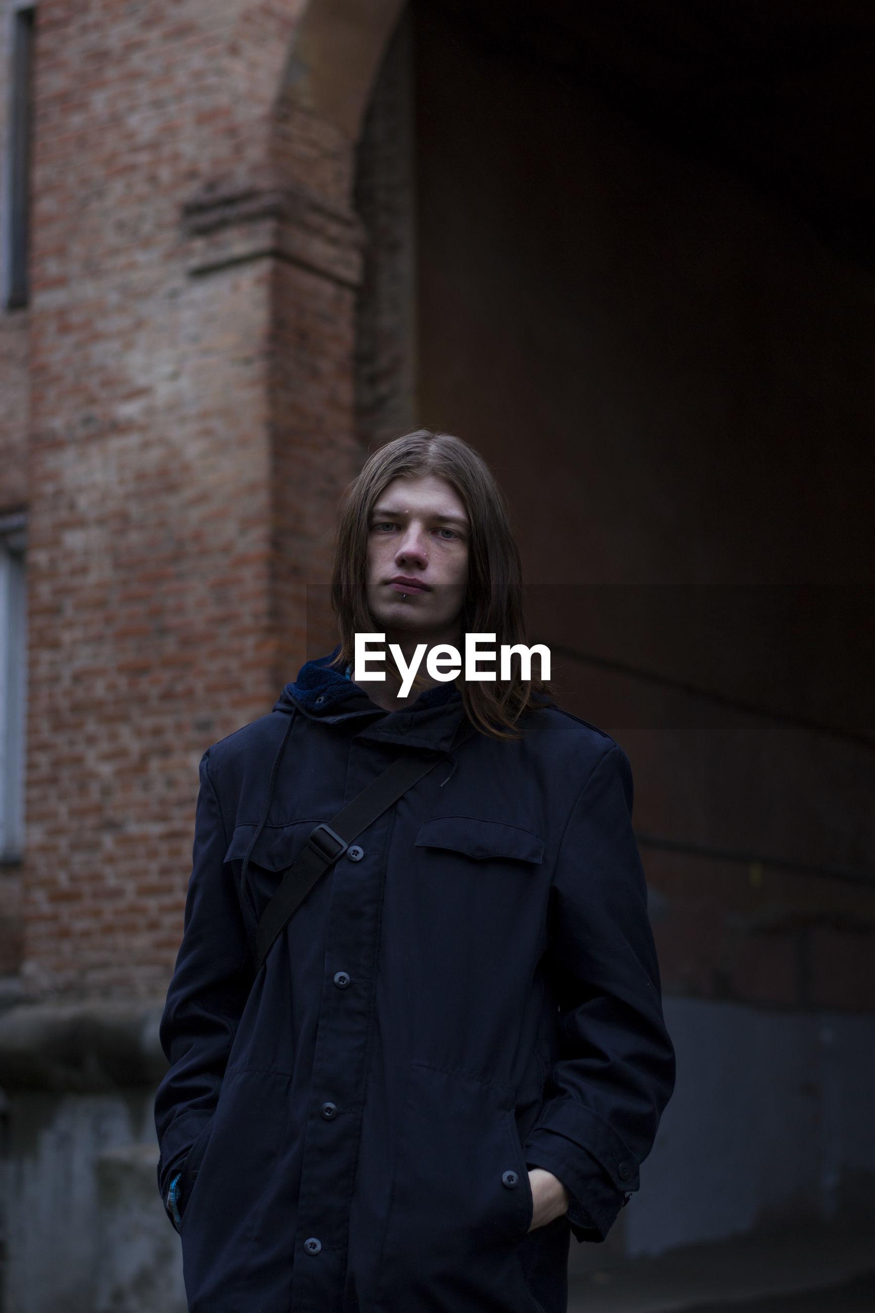 Portrait of man standing in front of brick building