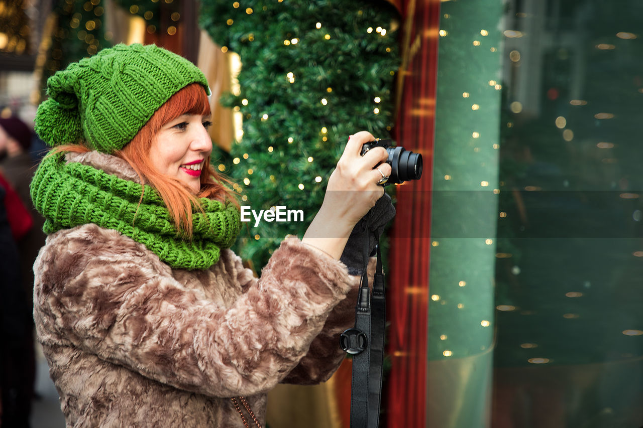 Close-Up Of Smiling Woman Photographing Through Camera