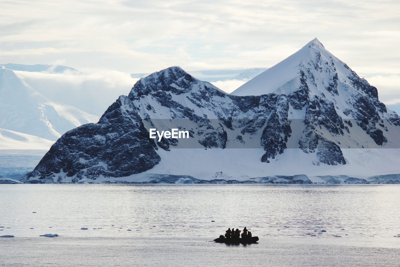 PEOPLE ON SNOWCAPPED MOUNTAIN AGAINST SEA