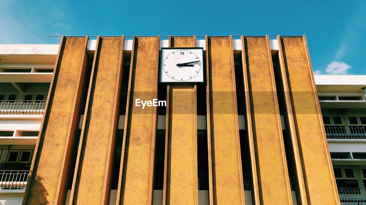 Low angle view of clock on building against sky