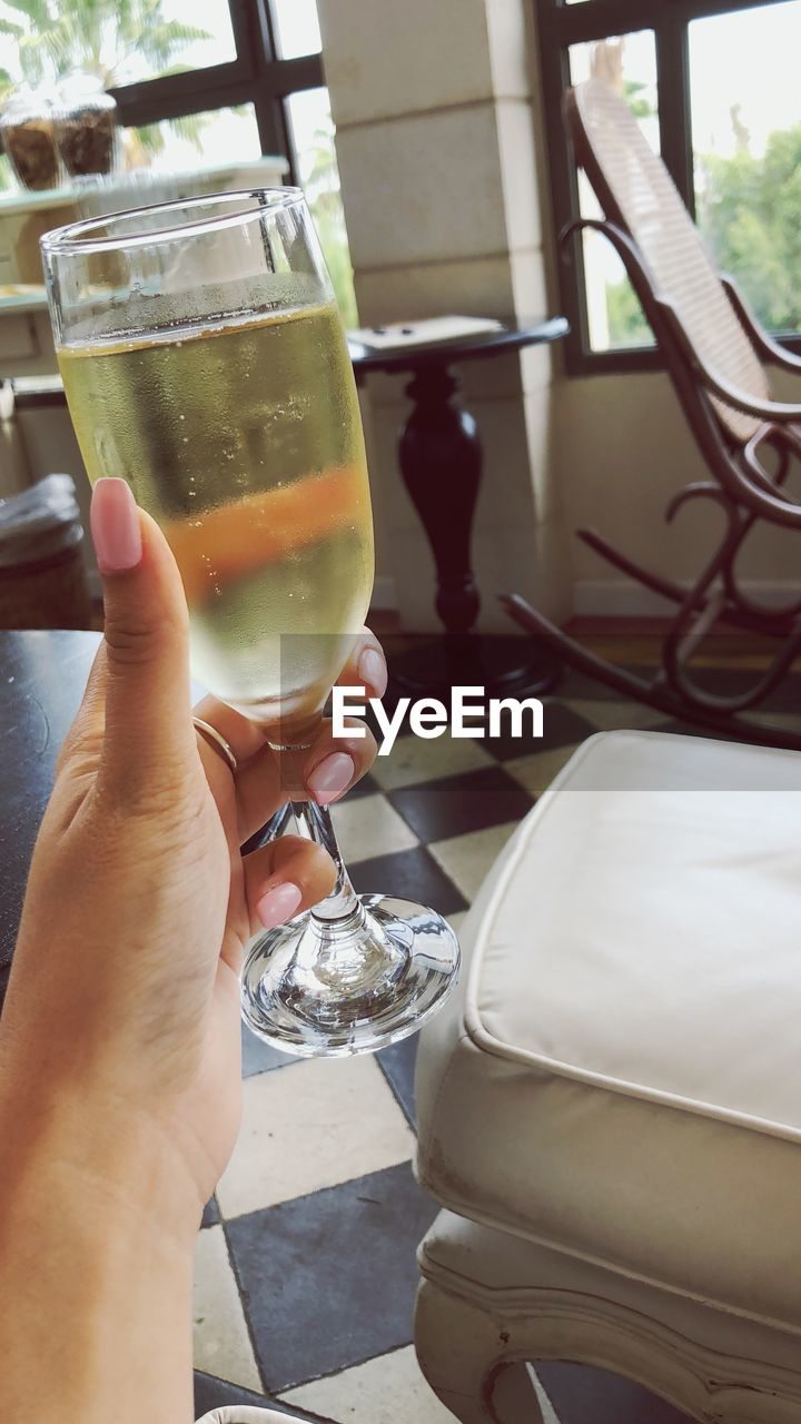 real people, human hand, hand, holding, human body part, lifestyles, drink, refreshment, glass, one person, food and drink, personal perspective, leisure activity, day, freshness, household equipment, drinking glass, close-up, unrecognizable person, finger