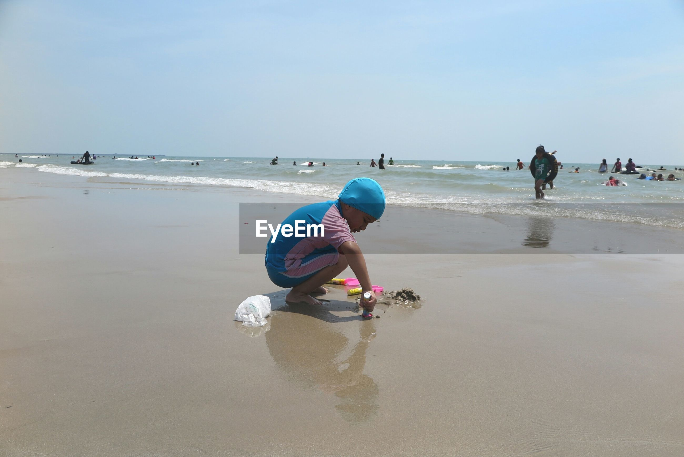 Side view of child playing at beach