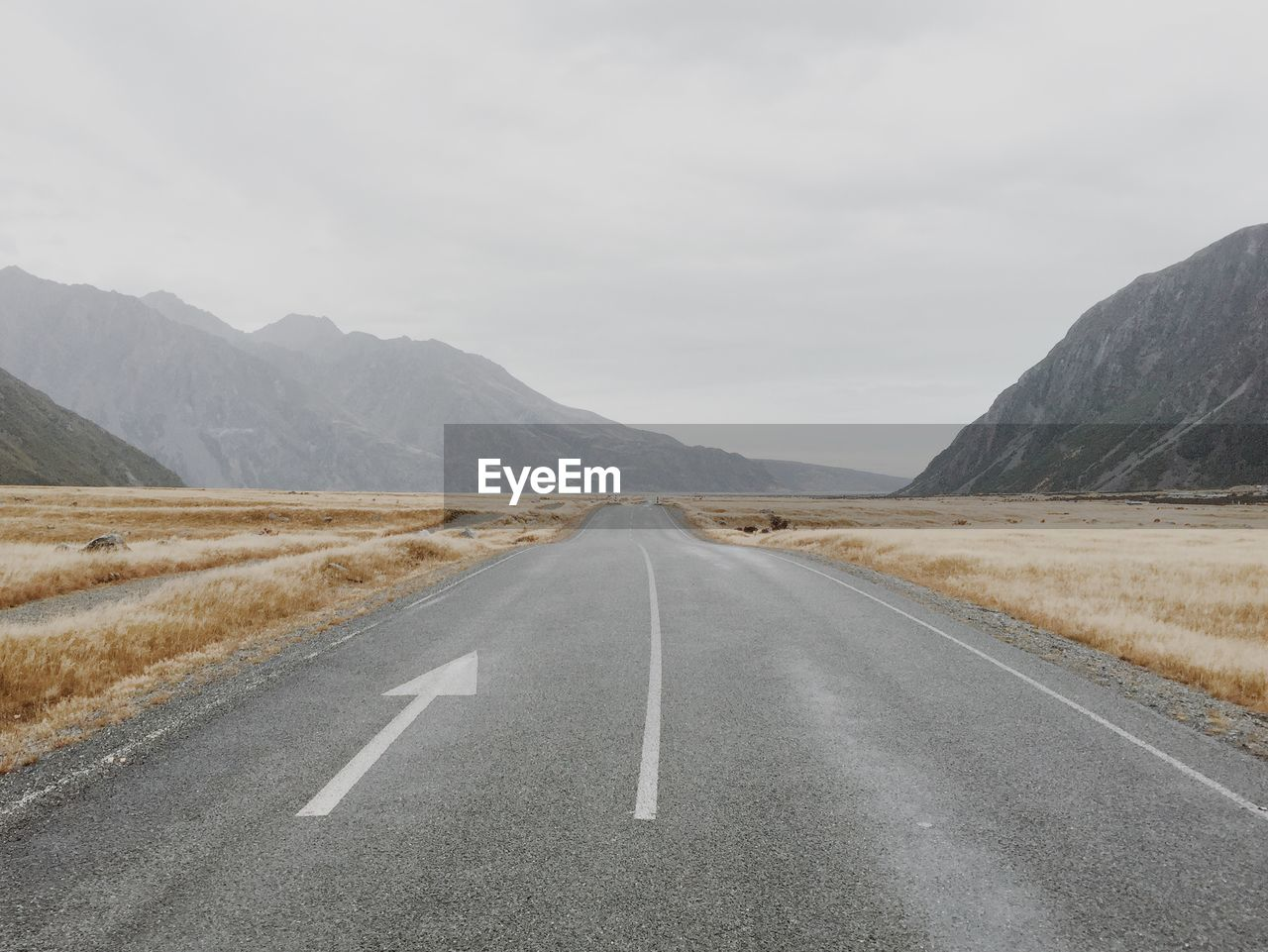 Empty Country Road Amidst Mountains Against Sky