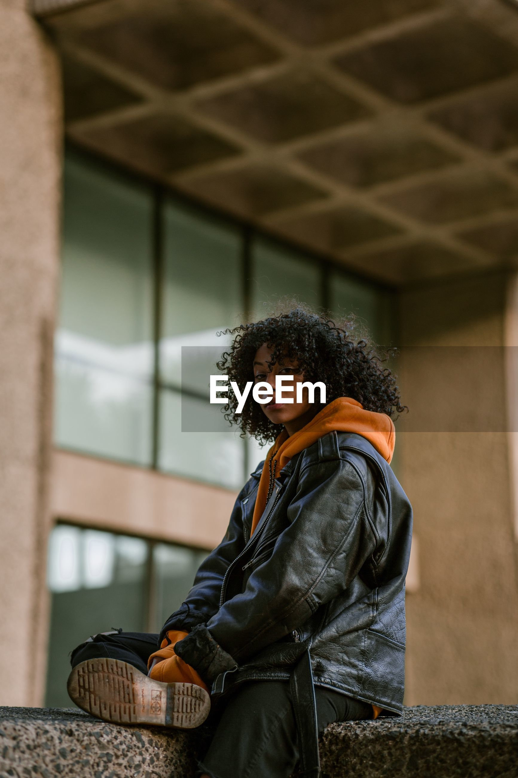 one person, three quarter length, real people, young adult, architecture, lifestyles, curly hair, clothing, built structure, jacket, casual clothing, leisure activity, standing, focus on foreground, music, portrait, wall - building feature, women, adult, hairstyle, outdoors, leather