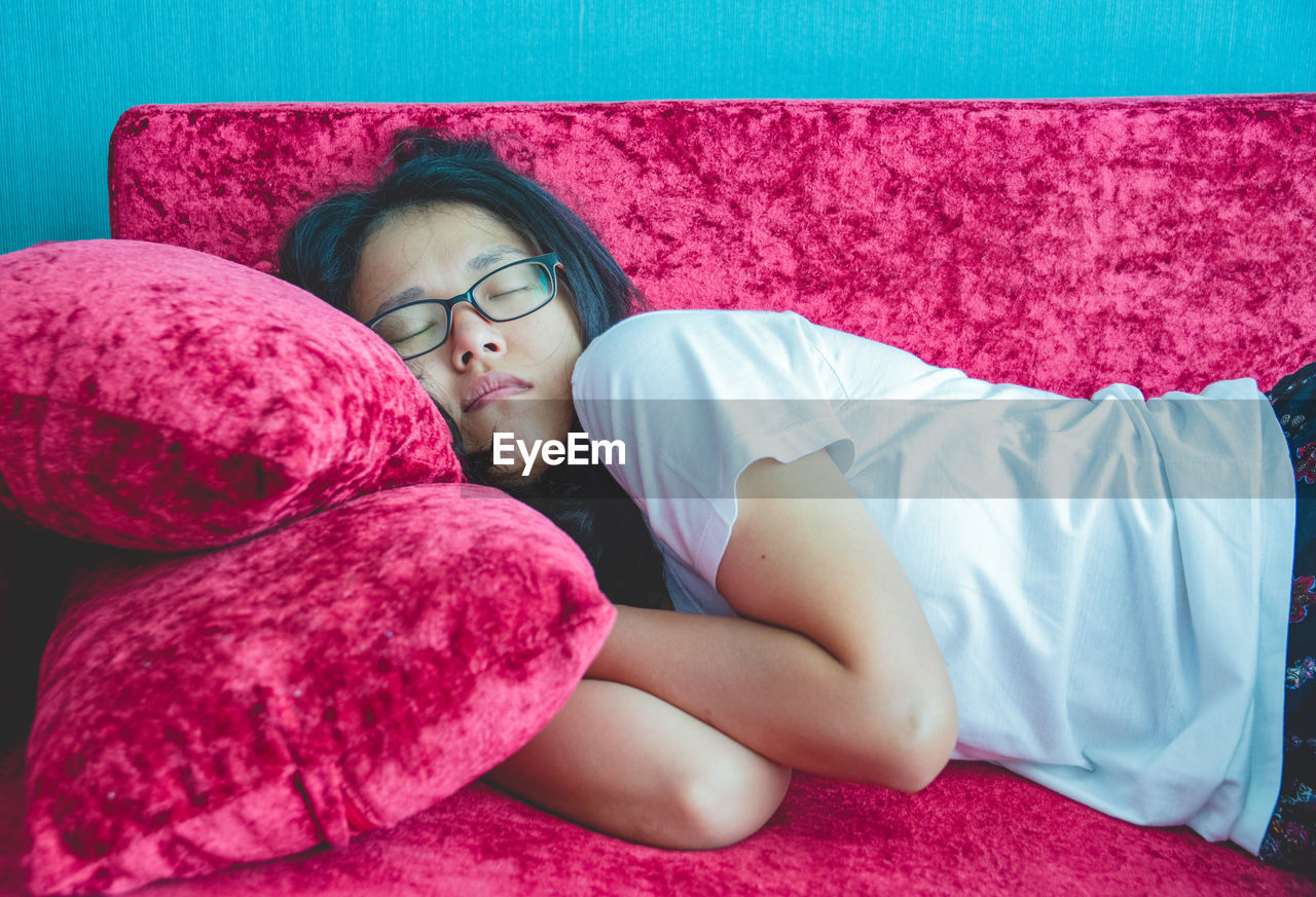 relaxation, lying down, one person, pink color, sleeping, furniture, bed, resting, real people, eyes closed, indoors, lifestyles, leisure activity, pillow, child, young adult, young women, women, childhood, innocence
