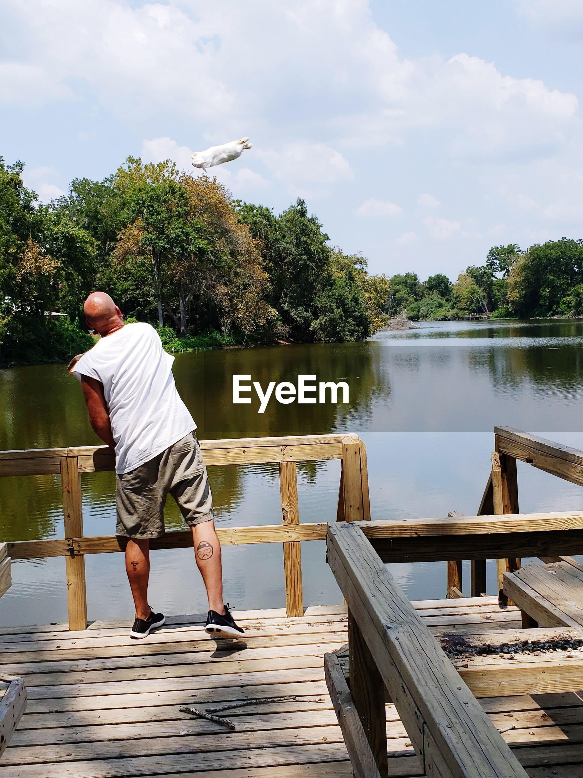 REAR VIEW OF MAN ON PIER OVER LAKE