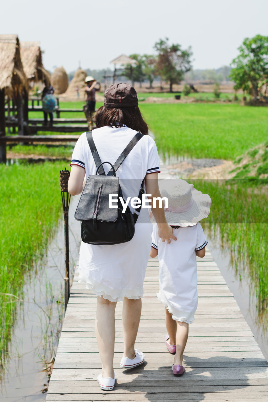 rear view, real people, women, walking, full length, adult, day, casual clothing, nature, lifestyles, plant, two people, people, footpath, leisure activity, the way forward, direction, outdoors, focus on foreground, clothing, hairstyle
