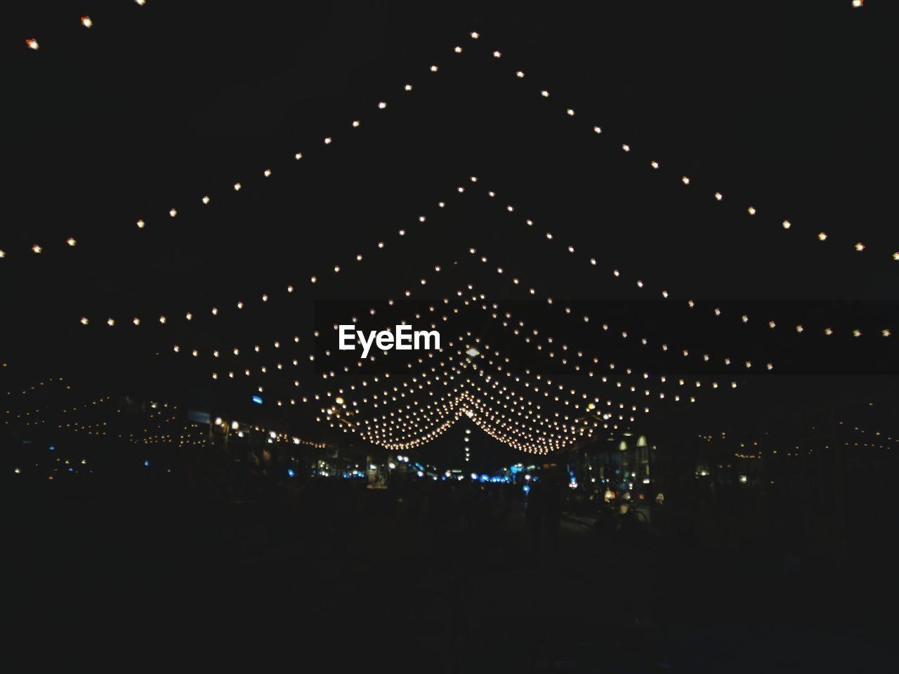 Illuminated decoration against sky at night