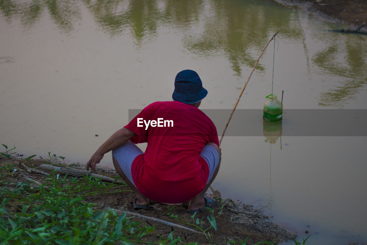 water, real people, one person, rear view, men, full length, fishing, lifestyles, sitting, lake, nature, casual clothing, clothing, leisure activity, crouching, activity, day, hat, outdoors, hood - clothing, warm clothing