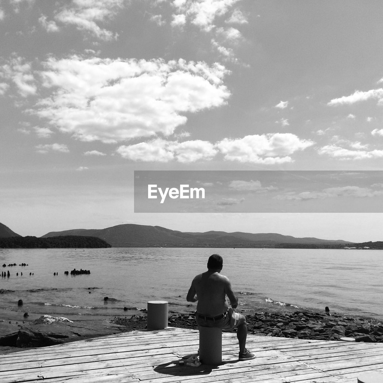Rear view of man sitting on pier against sky