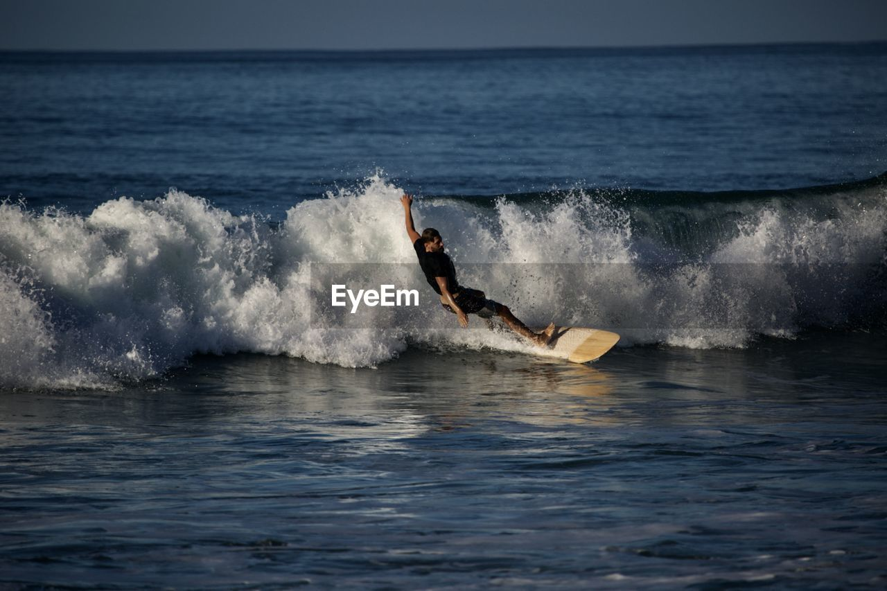 sea, water, motion, aquatic sport, sport, one person, surfing, wave, horizon over water, beauty in nature, horizon, waterfront, adventure, splashing, extreme sports, scenics - nature, nature, sky, skill, outdoors, power in nature
