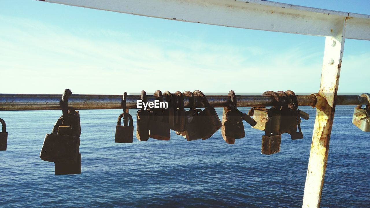 water, sky, hanging, no people, security, sea, day, nature, lock, safety, protection, padlock, metal, cloud - sky, tranquility, railing, outdoors, close-up, wooden post