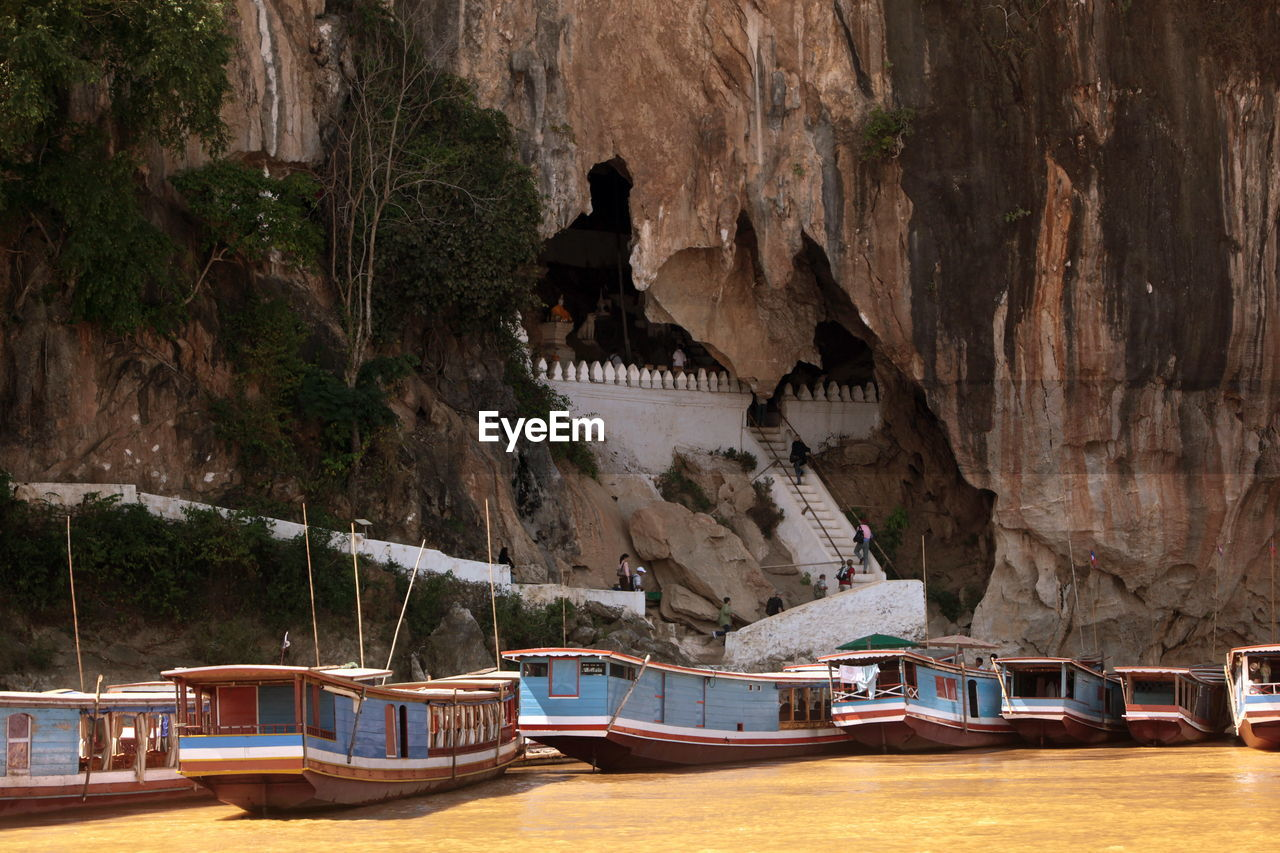 Boats moored on river against pak ou caves