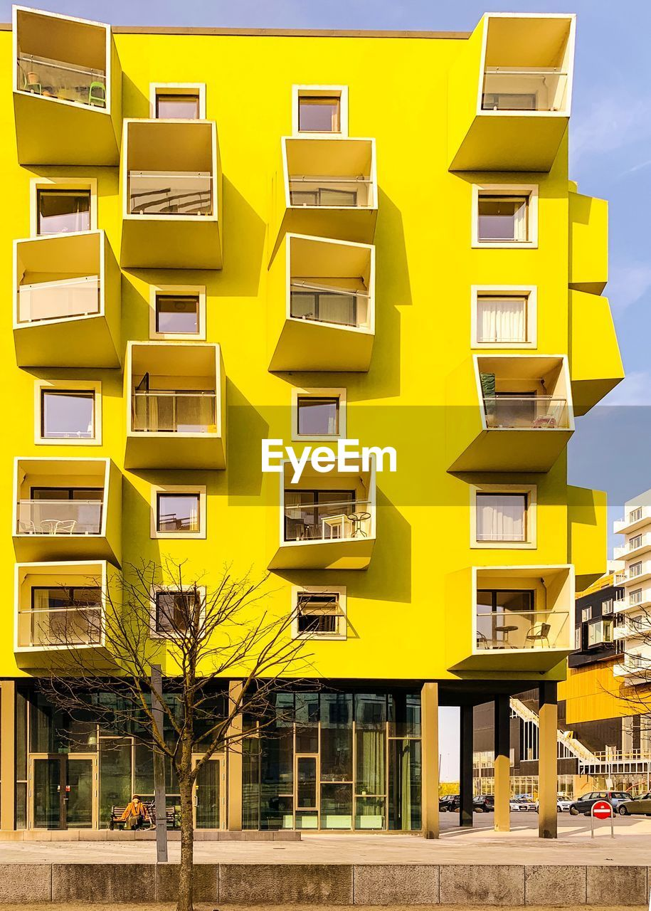 yellow, built structure, architecture, building exterior, residential district, building, city, no people, day, nature, outdoors, apartment, sunlight, city life, window, tree, street, sky, repetition, balcony, housing development