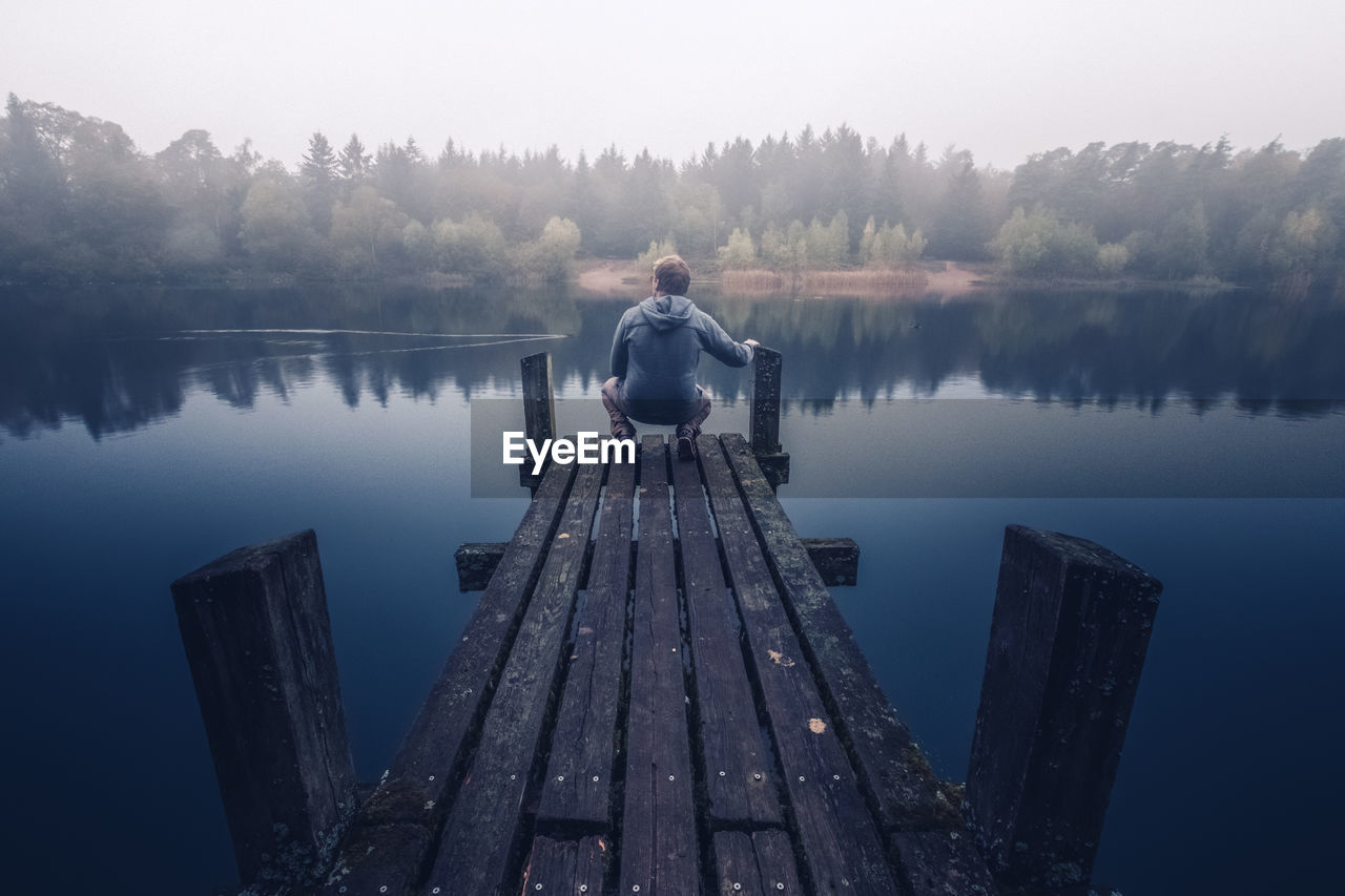 Man On Wooden Jetty Over Lake