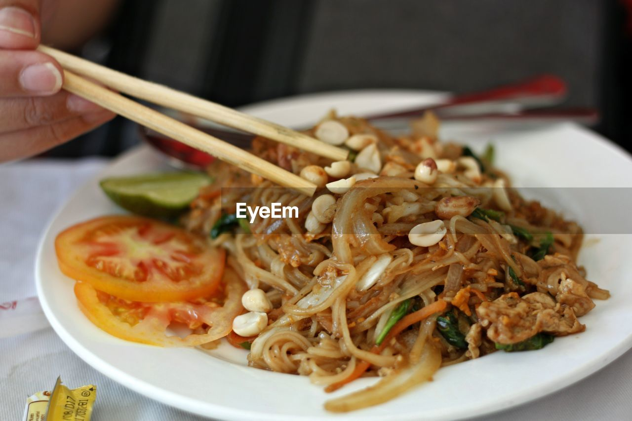 Cropped Image Of Person Having Food Using Chopsticks