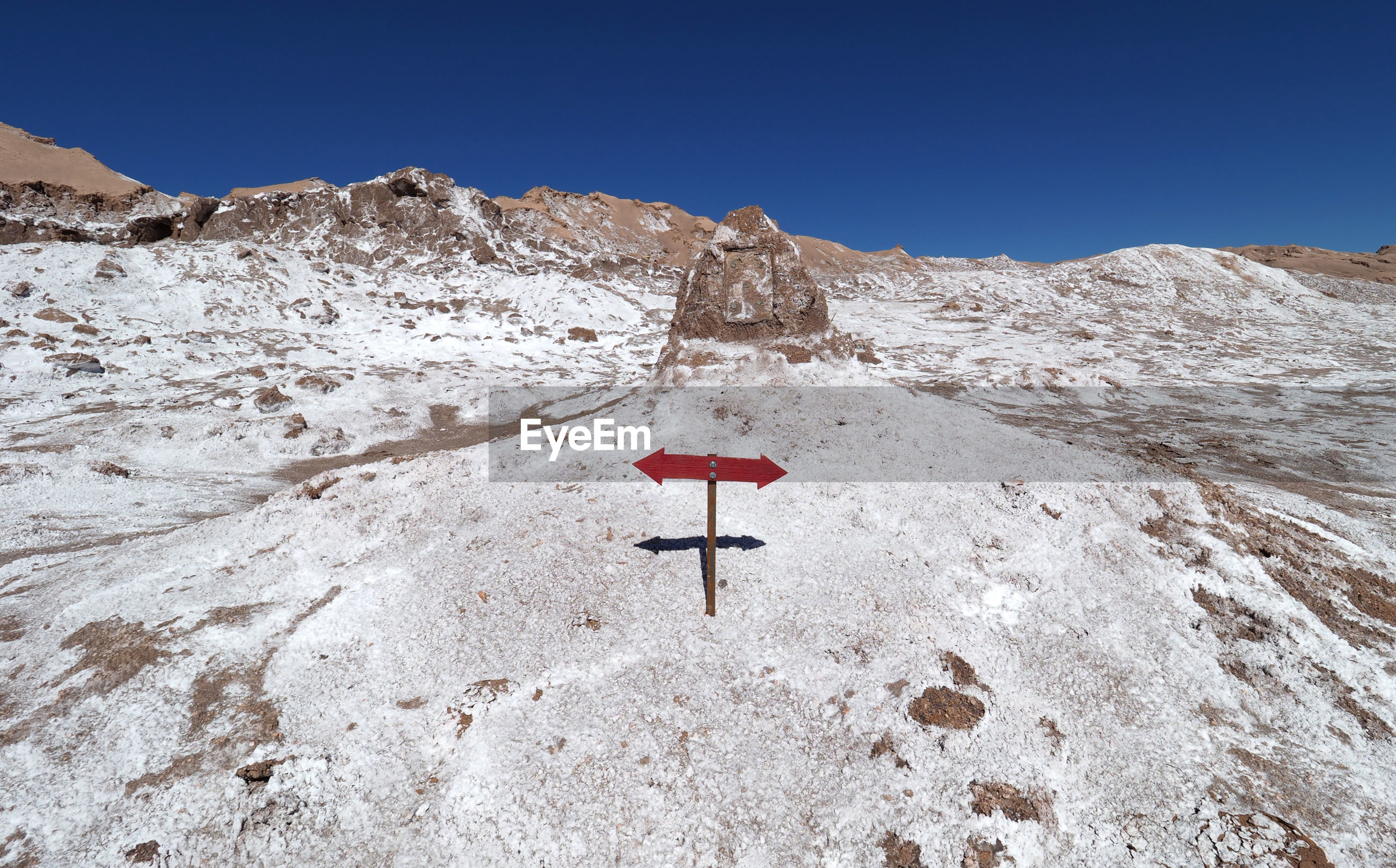 LOW ANGLE VIEW OF ROAD SIGN ON MOUNTAIN AGAINST SKY